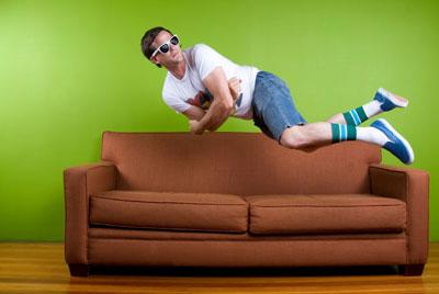 man jumps on sofa